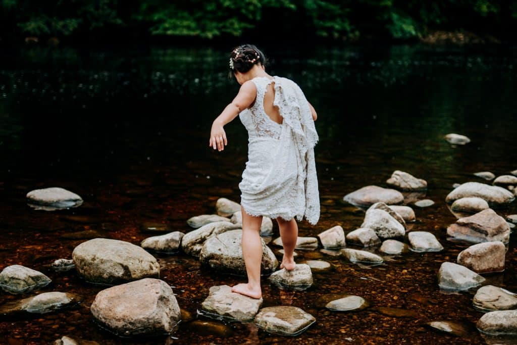 bride walks barefoot through stream