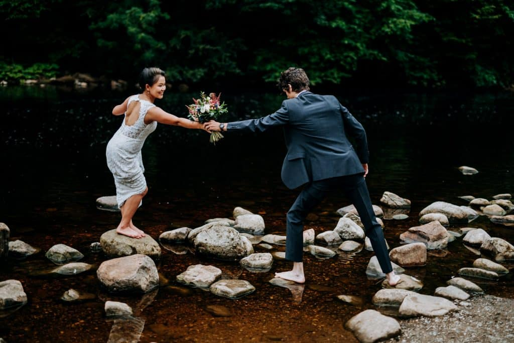 bride helps her husband onto the rocks in the middle of a stream at Bolton Abbey
