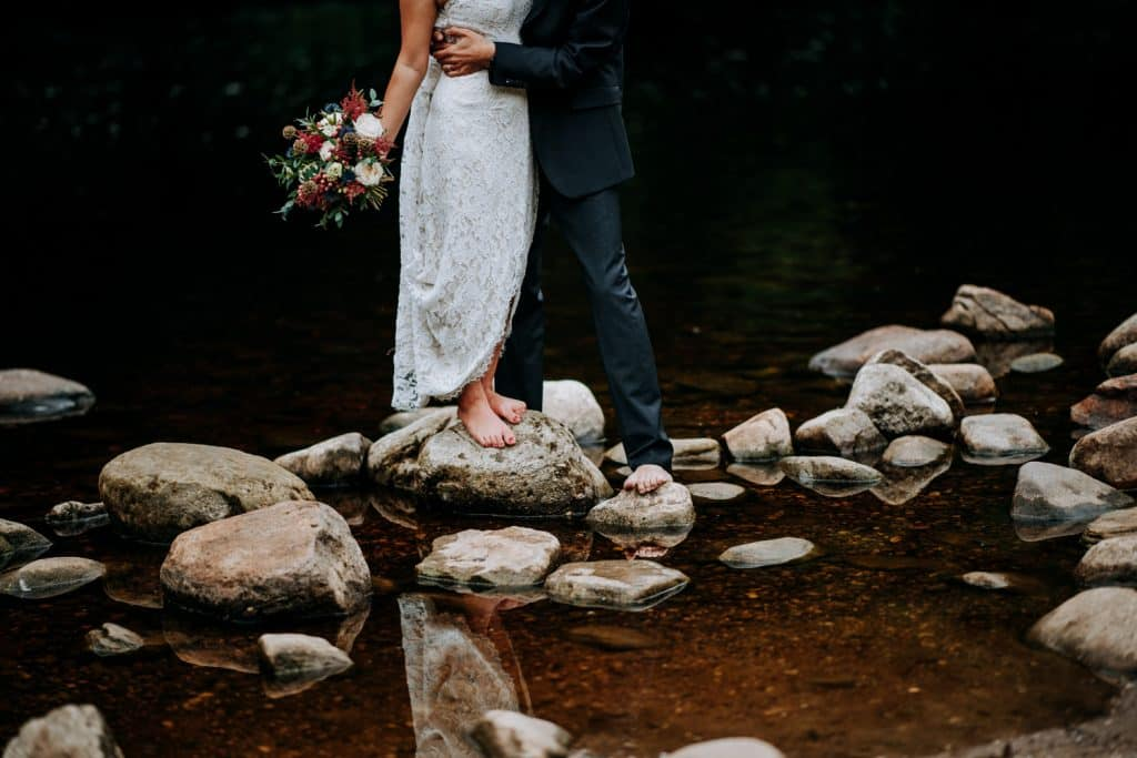 barefoot bride and groom in stream