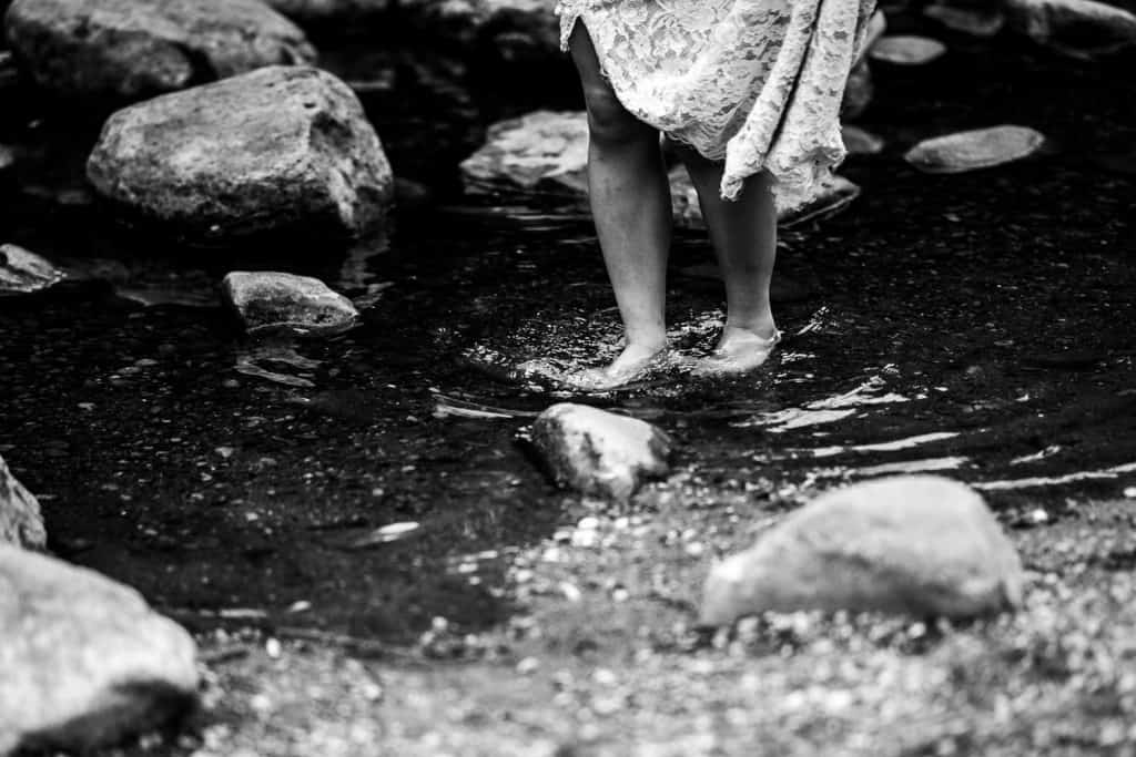 bride walks through the stream barefoot at Bolton Abbey