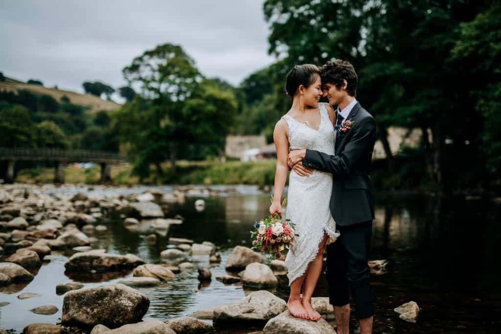 bride and groom rest faces together at bolton abbey