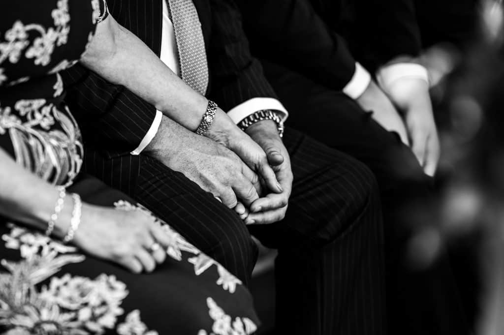 A black and white image of wedding guests holding hands