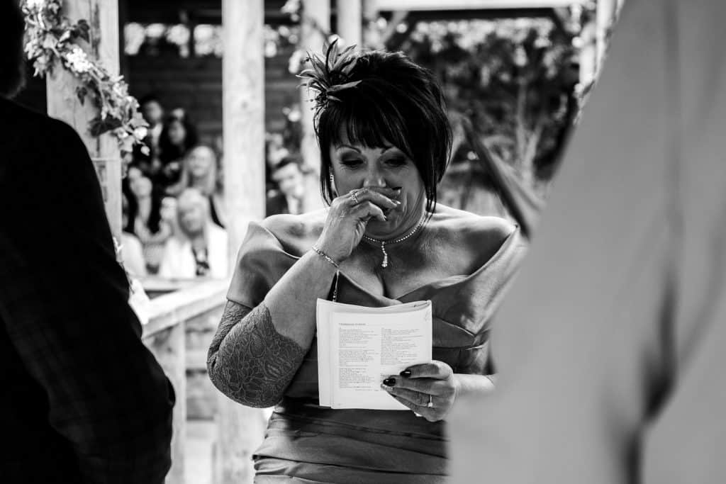 A woman becomes emotional while reading a poem at a wedding