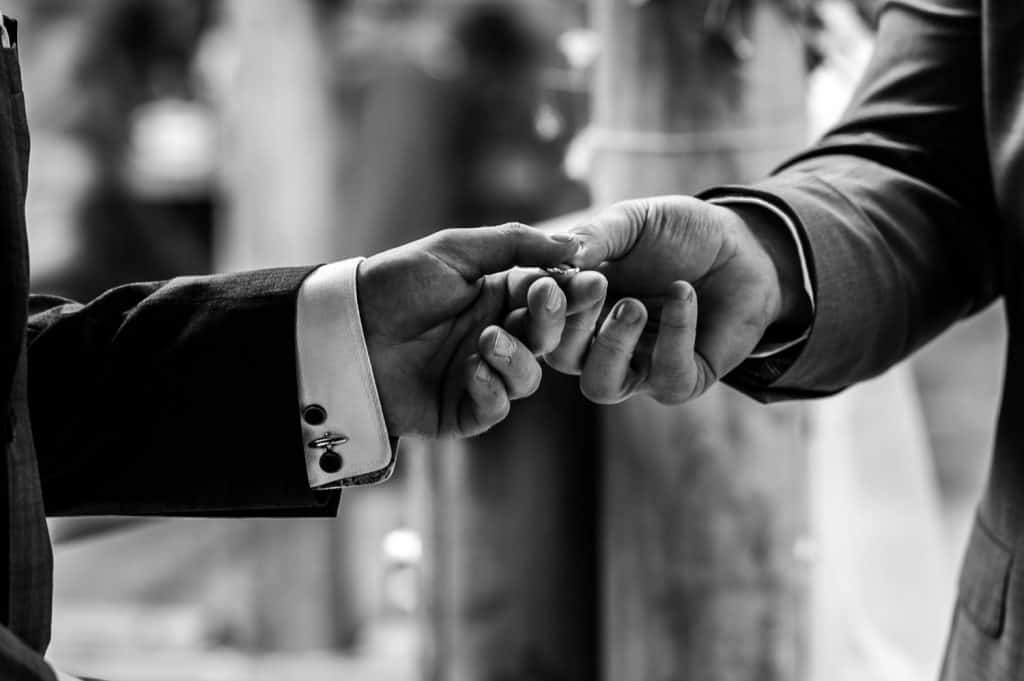 The best man hands the groom the wedding rings during a wedding ceremony