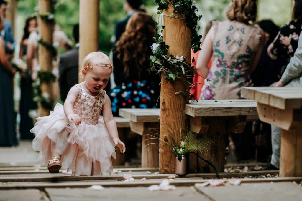 A flower girl runs happily at a Yorkshire wedding