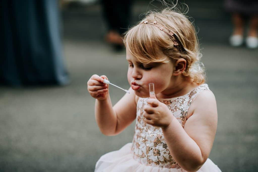 A flower girl blows bubble at a Yorkshire wedding