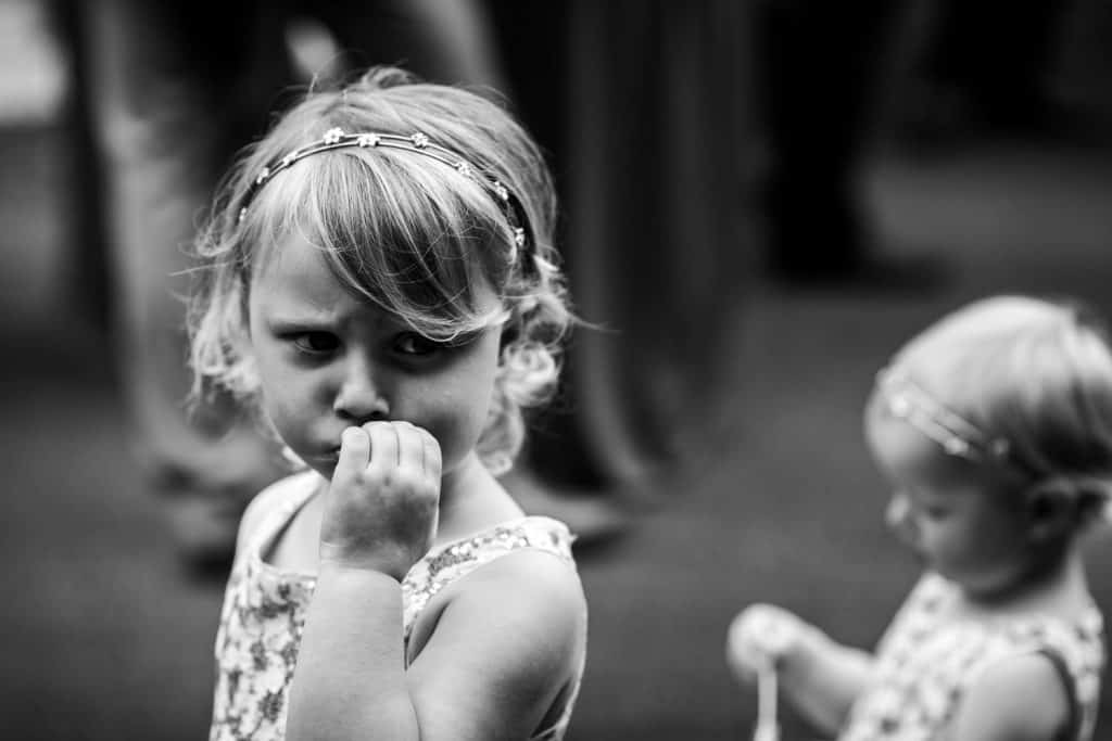 A flower girl captured in a black and white photograph at a wedding
