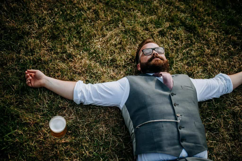A man in a suit falls asleep in the sun at a wedding