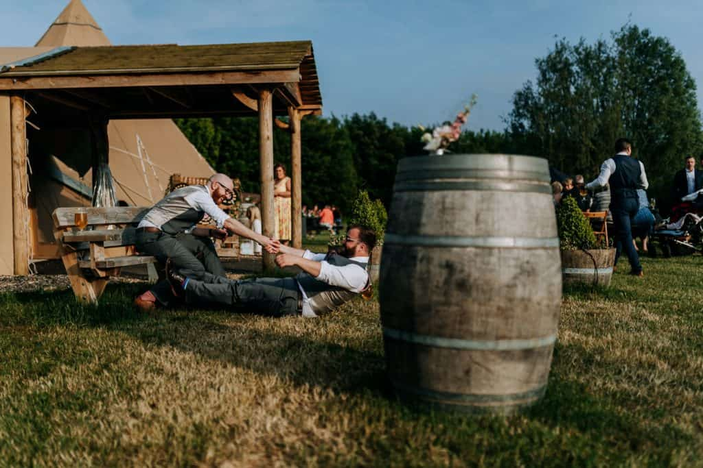 Two groomsmen have fun at a wedding in the sunshine