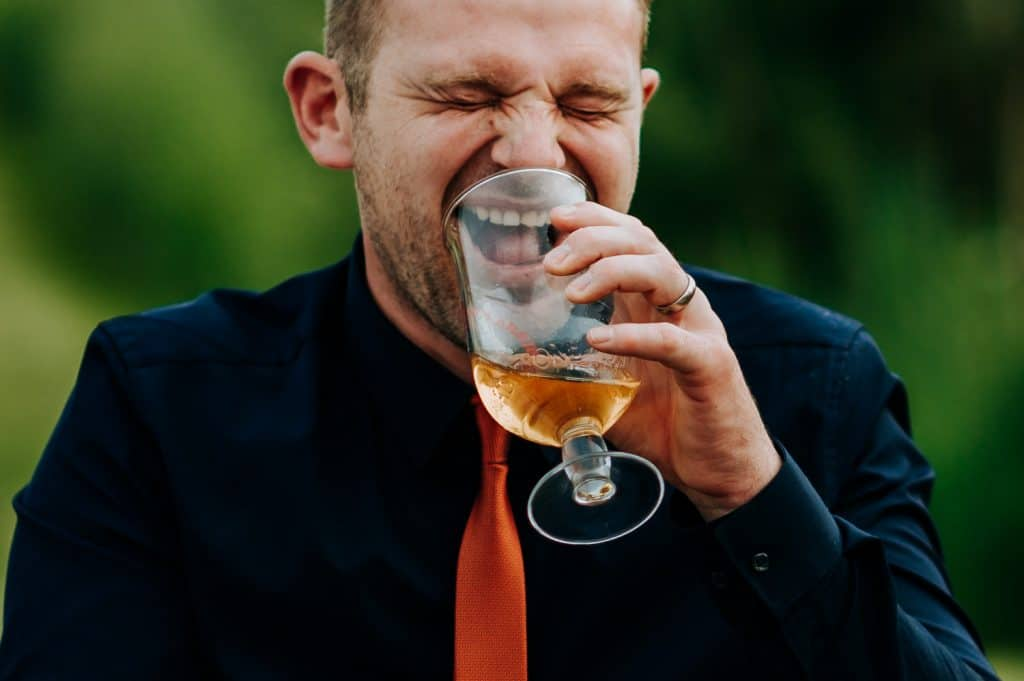 A man laughs uncontrollably into his pint glass