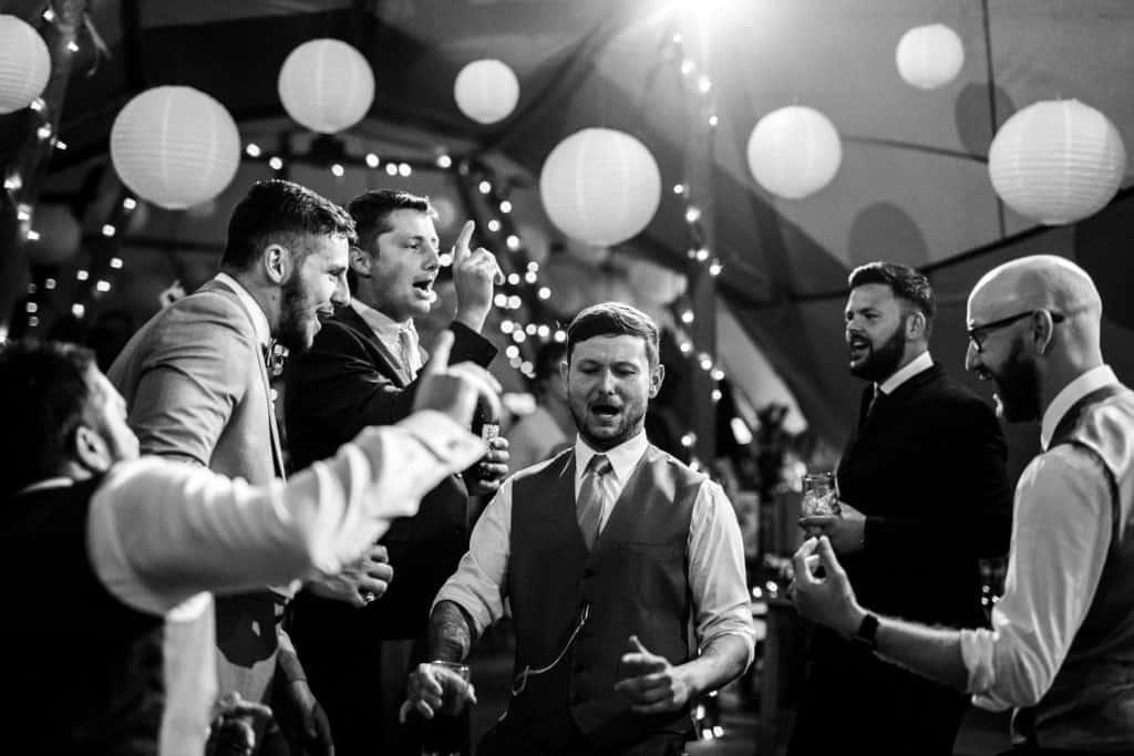 Male wedding guests dance together at a Yorkshire wedding