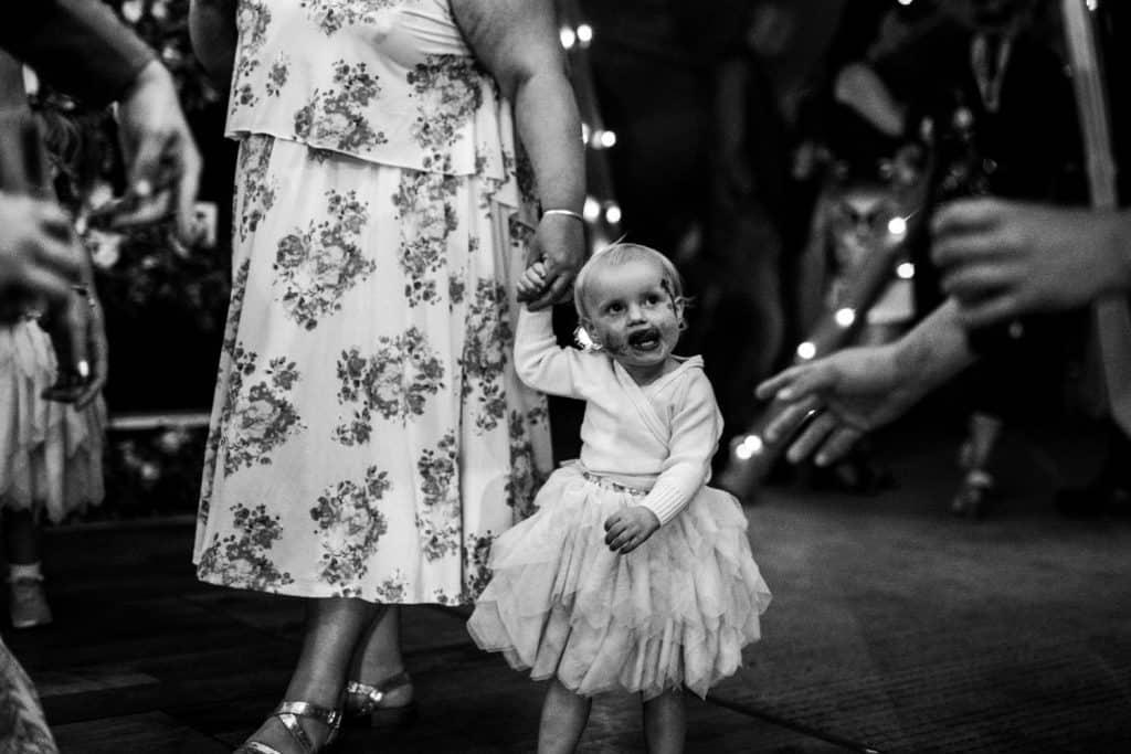 A flower girl enjoys the dancing at a wedding