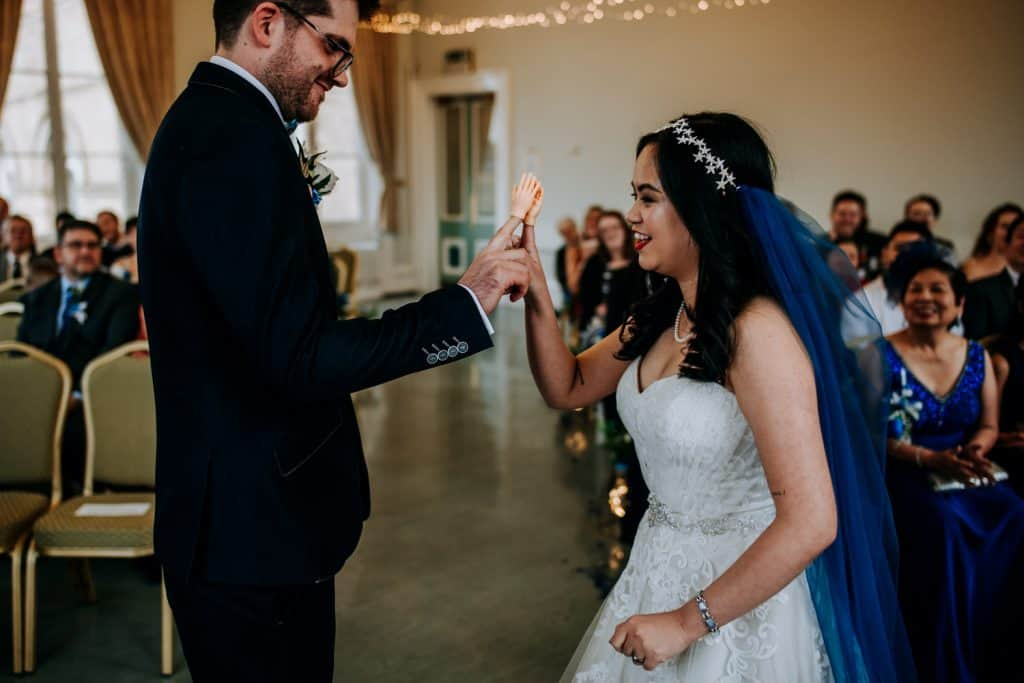 An image of a bride and groom high five-ing after getting married