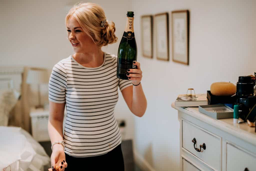 Bridesmaid pouring champagne in Cheshire