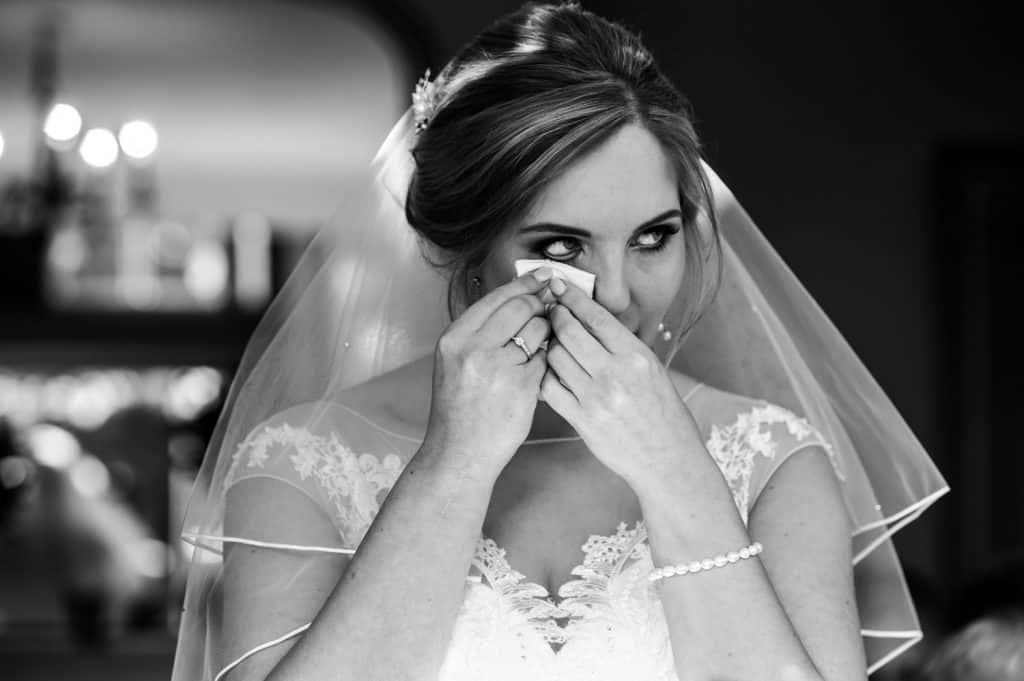 A bride wipes away a tear during her wedding ceremony