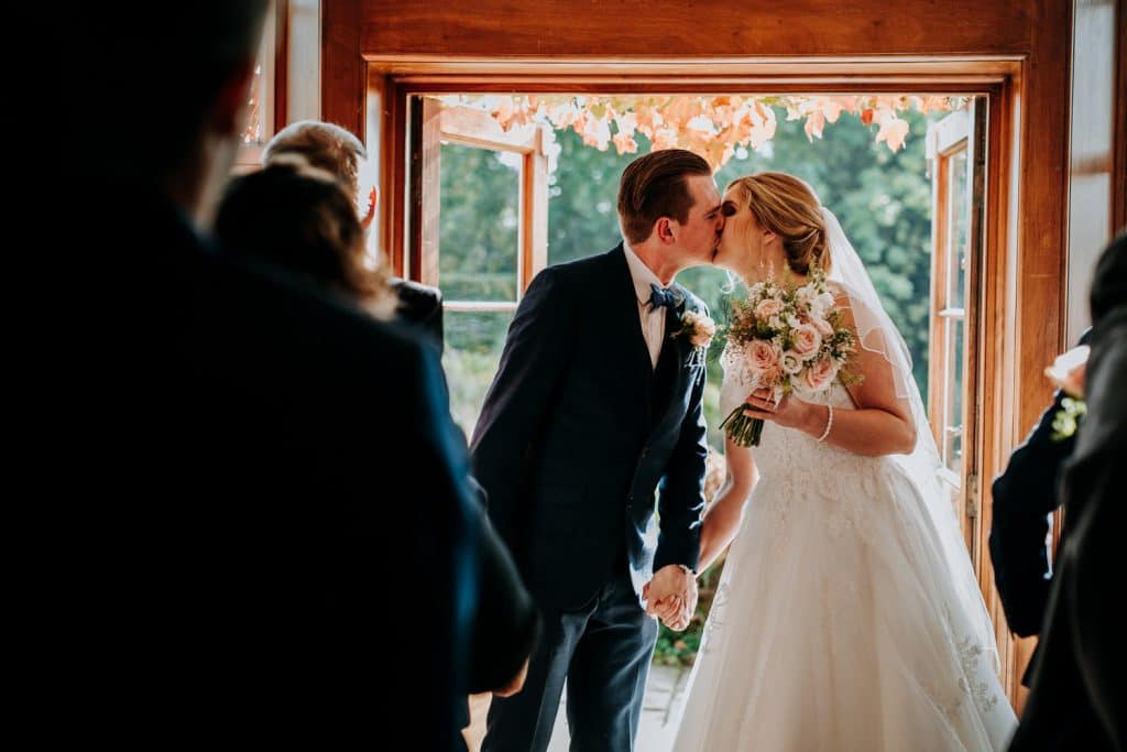 A bride and groom celebrate their wedding ceremony with a kiss