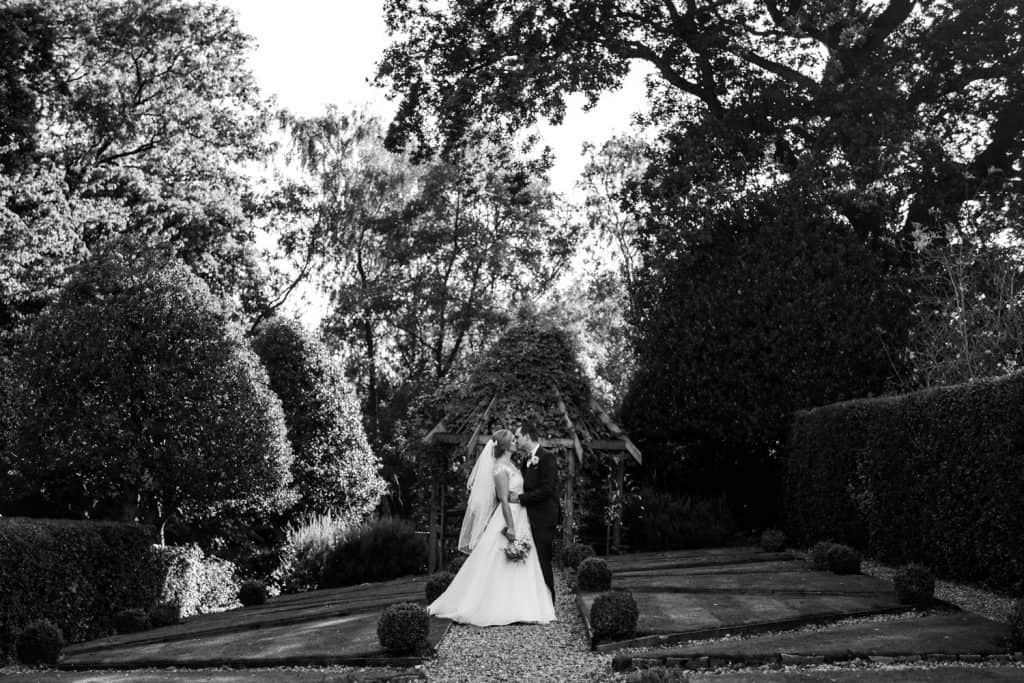 A black and white image of a bride and groom kissing in a beautiful English garden