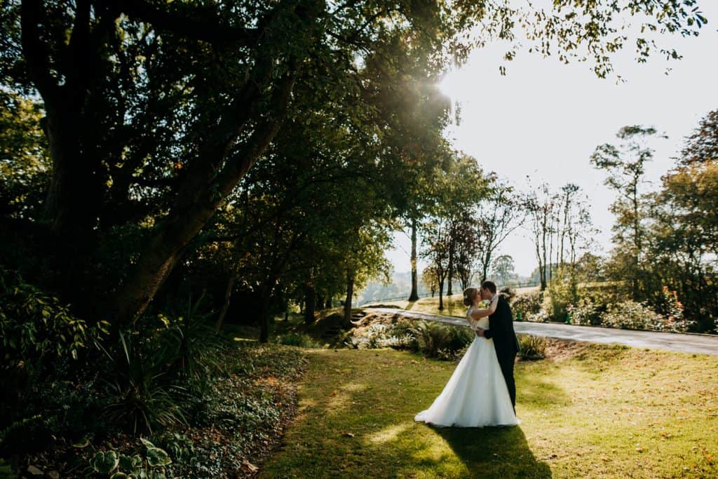 A bride and groom kiss as the sun sets slowly behind them