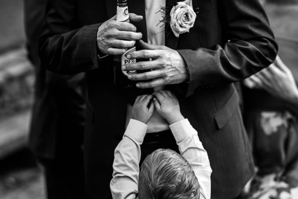 A page boy tries to steal his dad's bottle of peroni