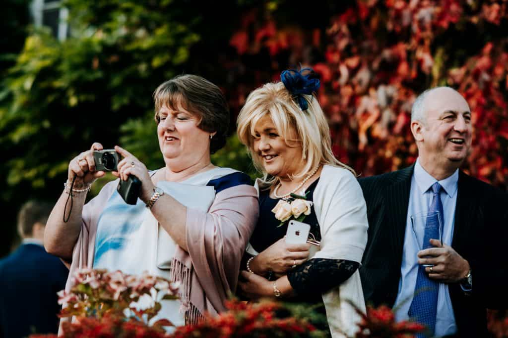 Wedding guests take photos of the happy couple