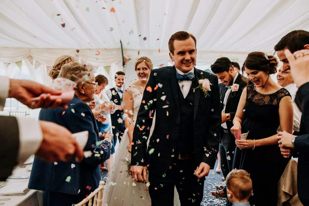 A bride and groom are showered in confetti inside a wedding marque