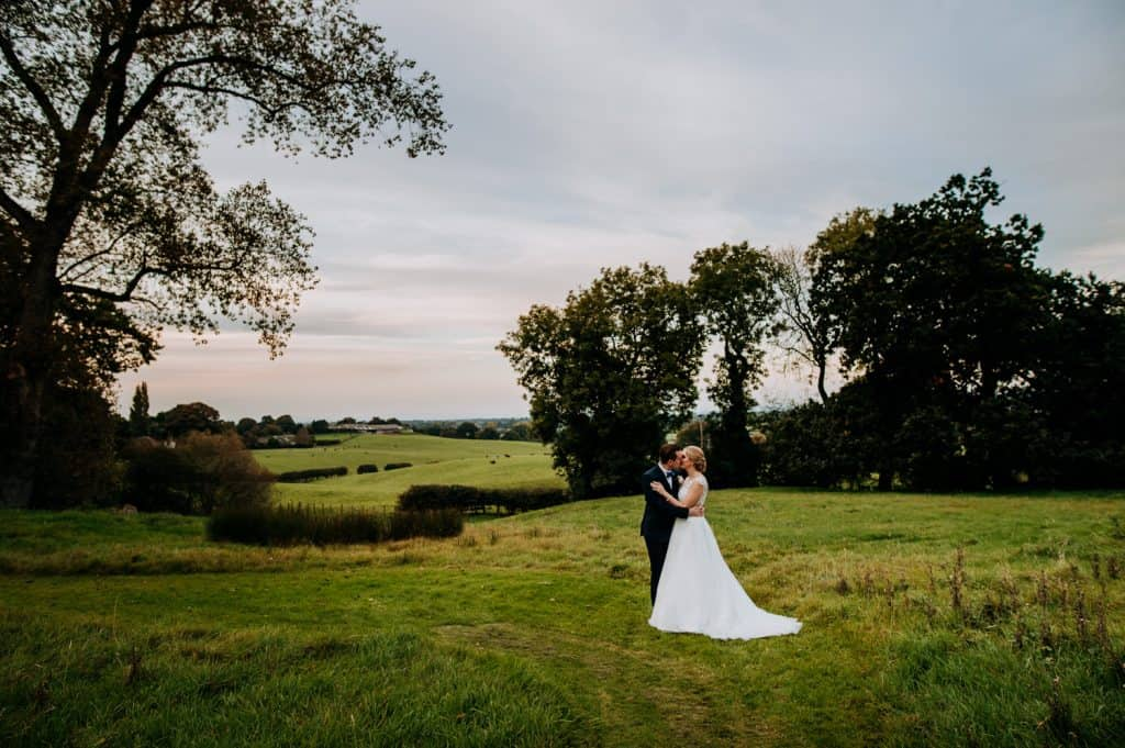 A bride and groom within a beautiful green field