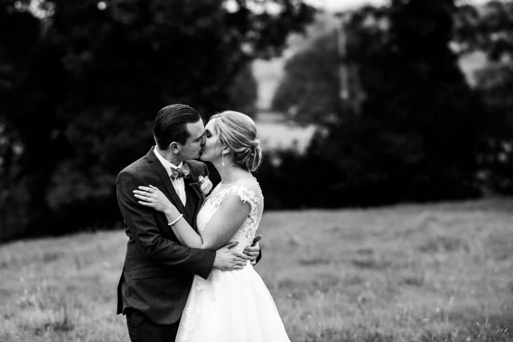 A bride and groom kiss in the grounds of a Cheshire wedding venue