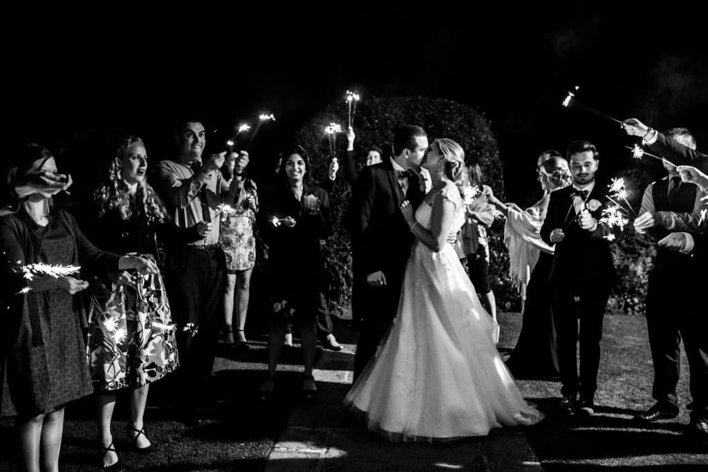 A black and white image of a bride and groom and sparklers