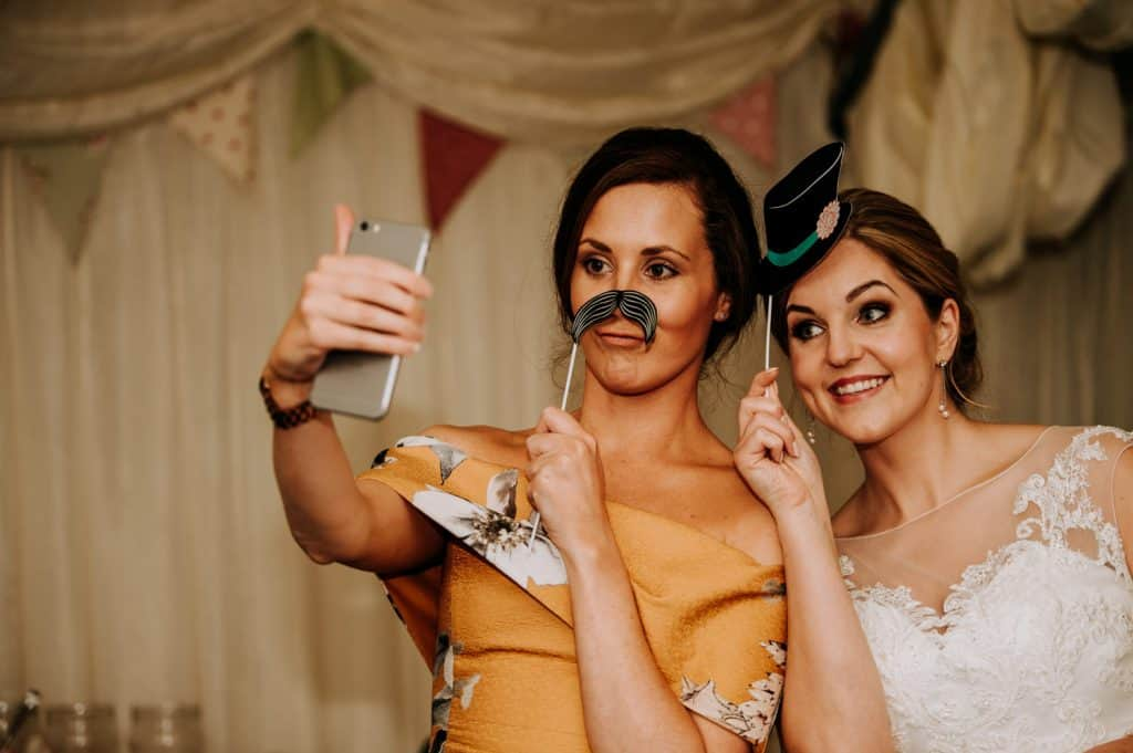 Wedding guests play around with funny props
