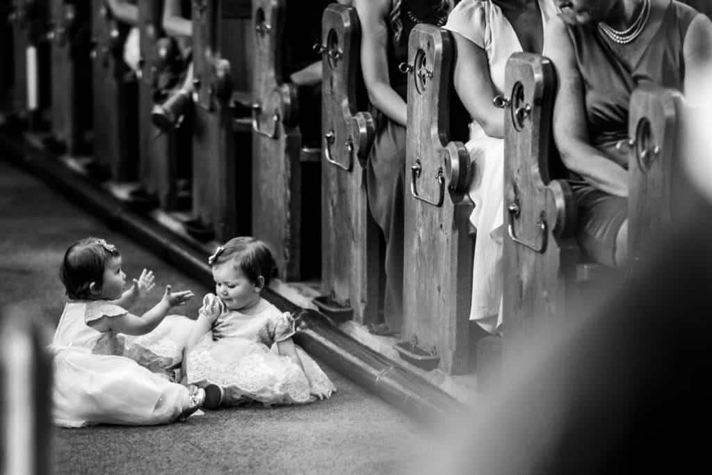 Two children play during a church wedding ceremony