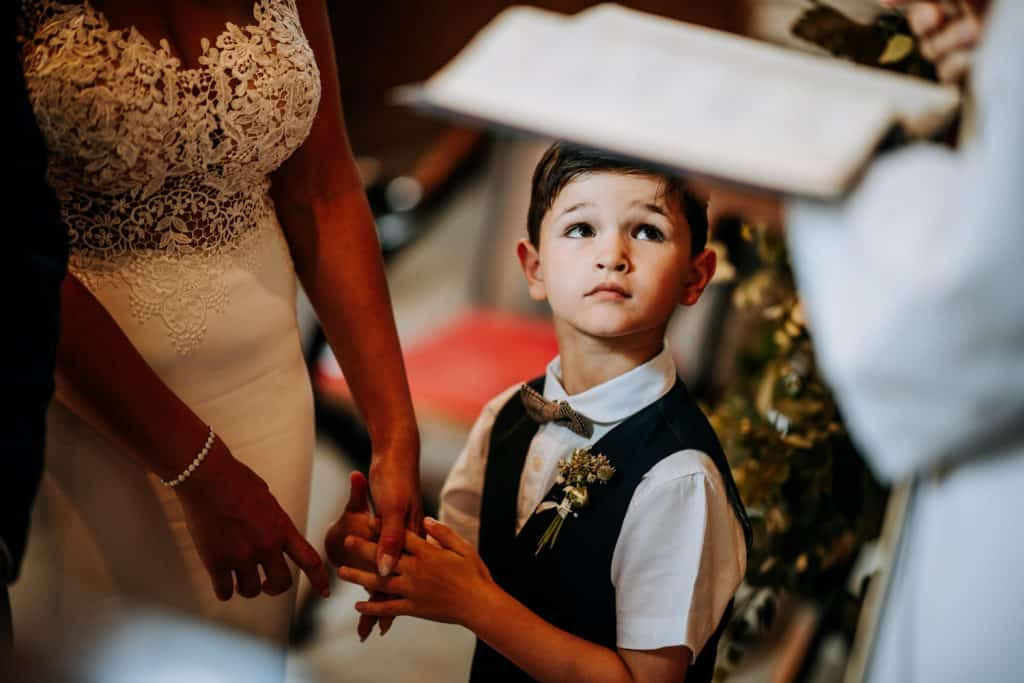 The bride's son holds her hand at a church wedding