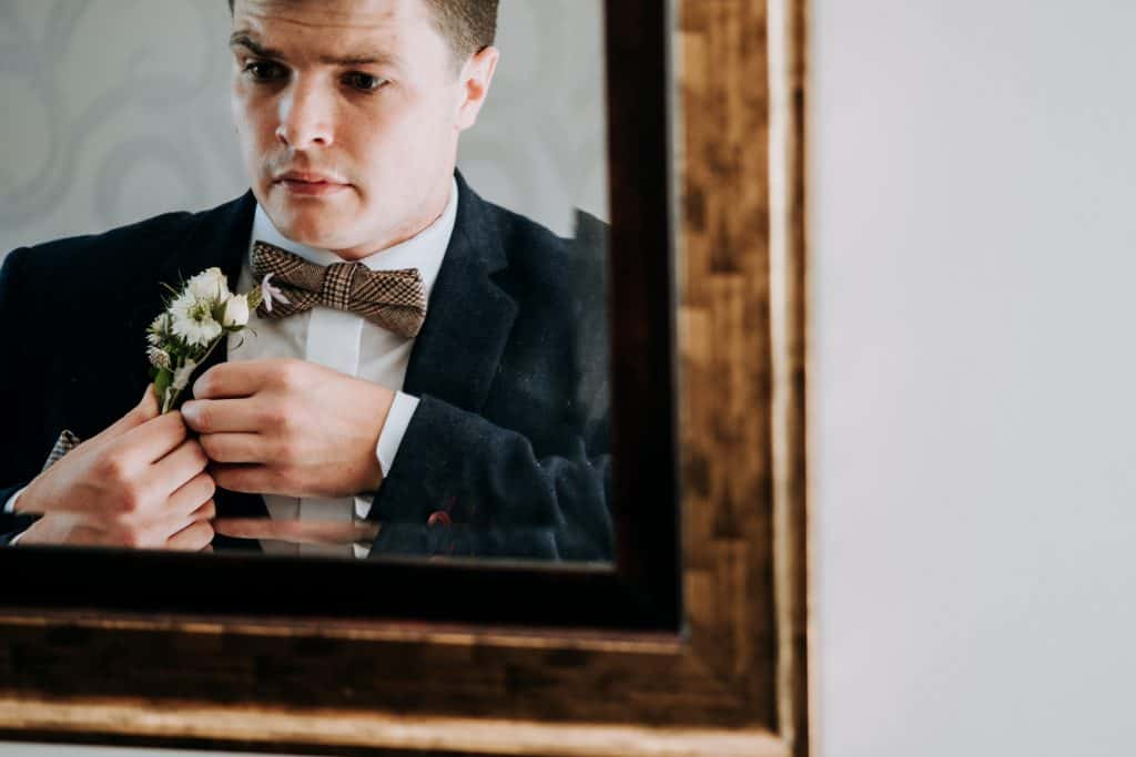 Groom puts on his buttonhole in mirror