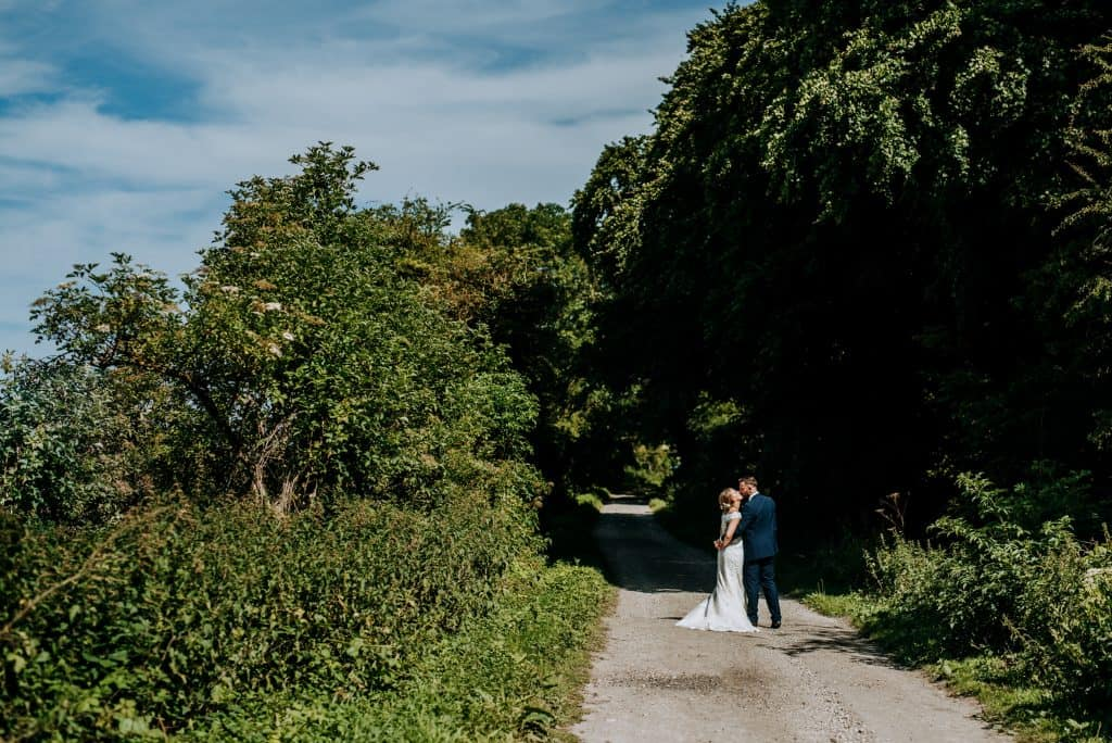 the couple take a romantic stroll around Little Wold Vineyard