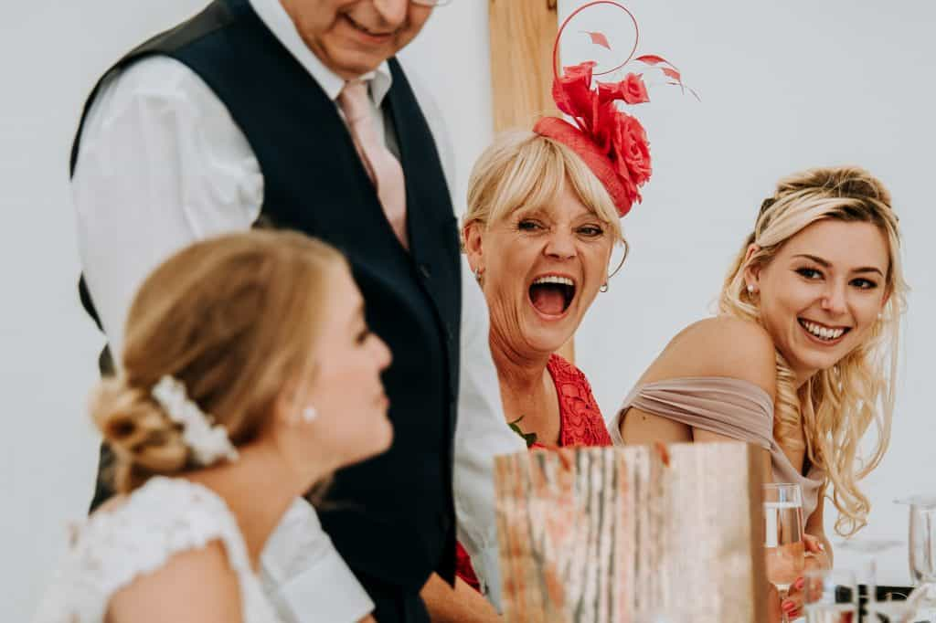 mother of the bride wearing a red fascinator laughs during wedding speeches