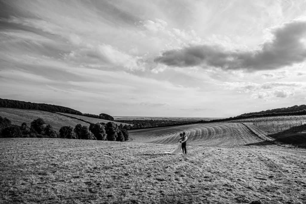 a couple kiss in the Yorkshire Wolds underneath a dramatic sky
