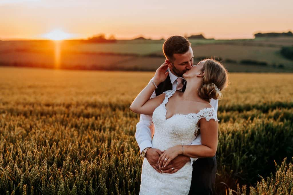 Bride and good kissing as the golden sun sets at Little Wold Vineyard