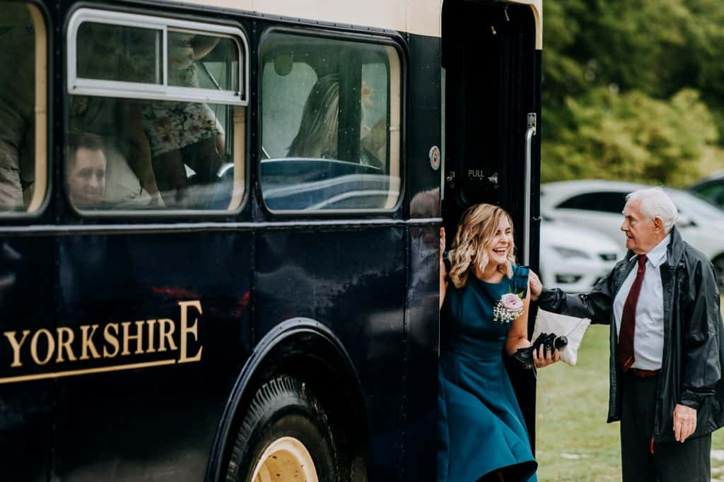 Wedding guests arrive by vintage yorkshire bus
