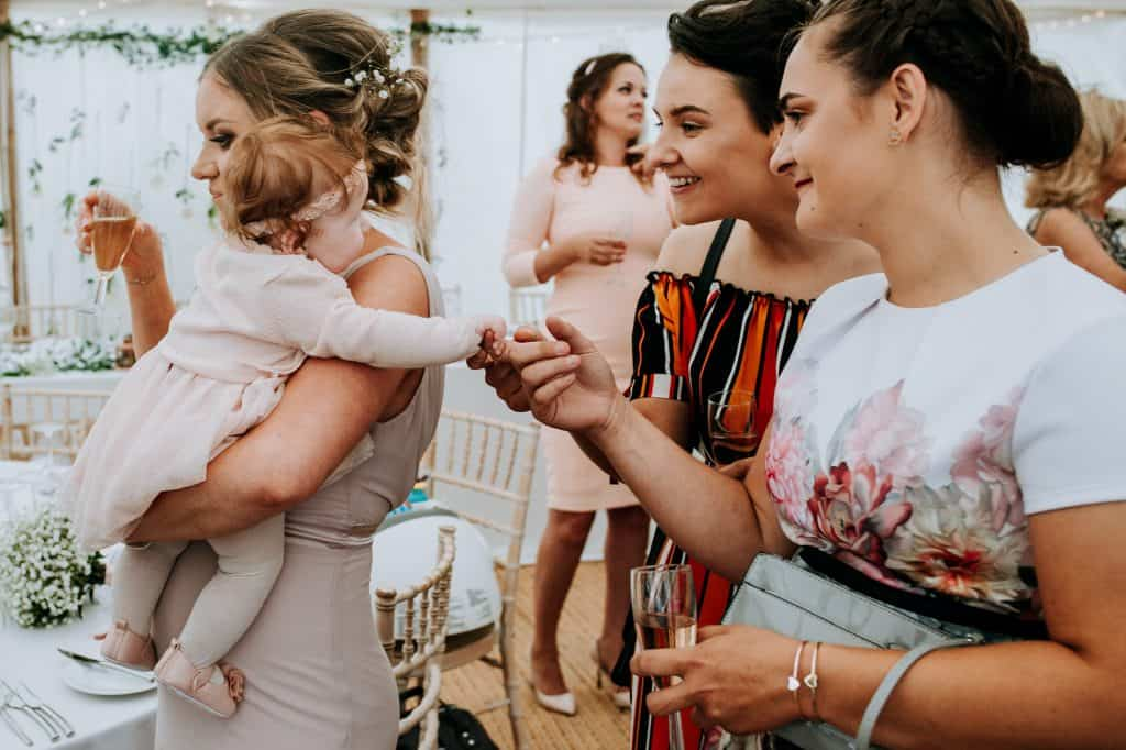 ladies cooing over a cute baby girl at a marquee wedding