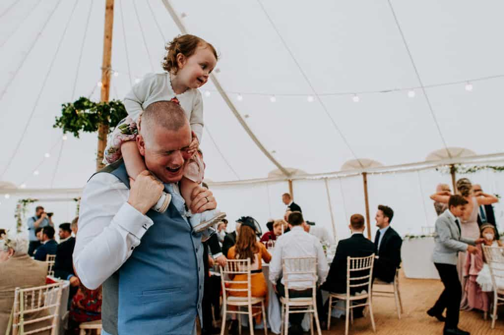 little girl on her dads shoulders  is accidentally poking him in the eye