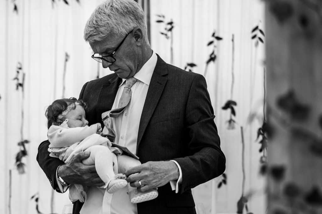a tender moment captured by m and g wedding photography a granddad cuddles tiny baby