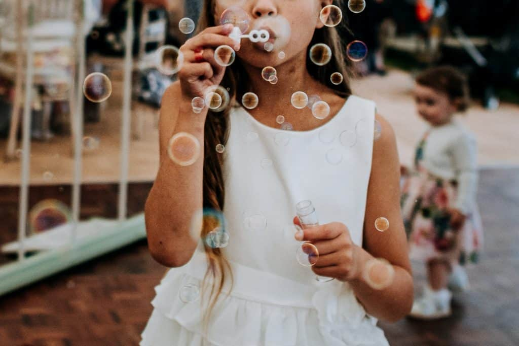 flower girl is blowing bubbles