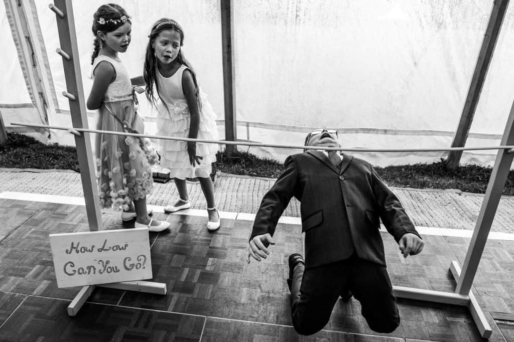 two flower girls watch on as young boy shows off his limbo skills