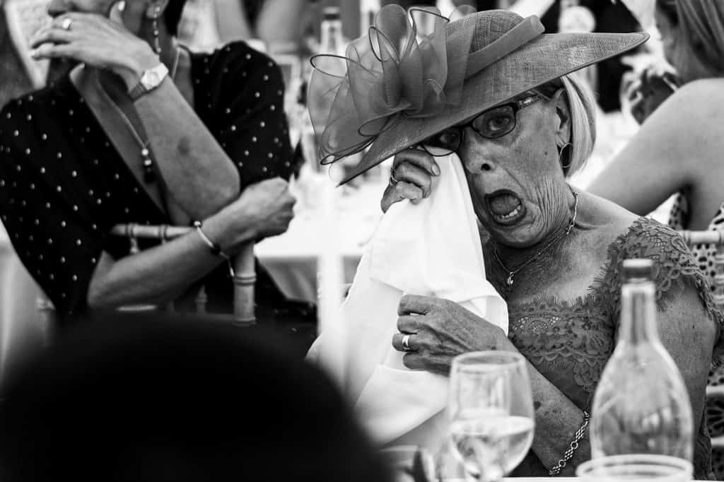 A woman wearing a beautiful hat cries during  the wedding speeches