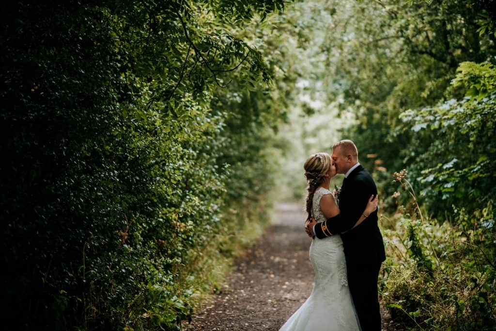 a bride and groom kiss in the rain at  Little wold vineyard