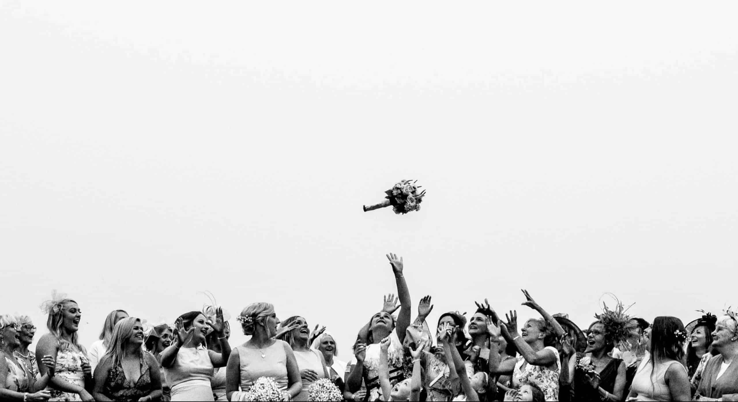 award winning image by m and g wedding photography all the women at the wedding gather together for a bouquet toss