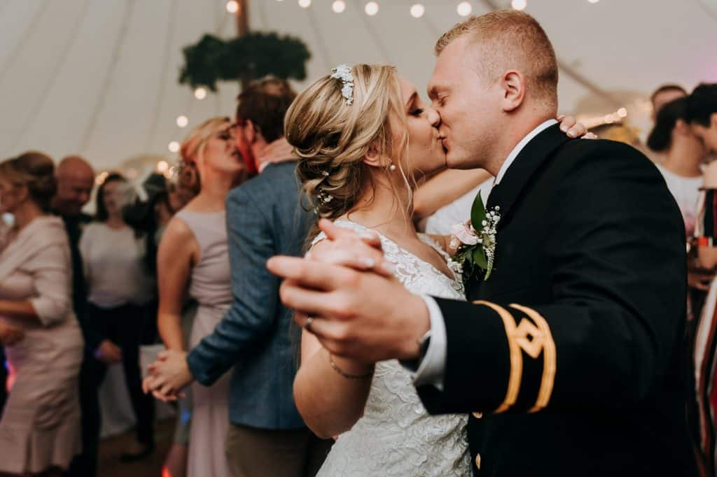 a bride and groom share a kiss during their romantic first dance
