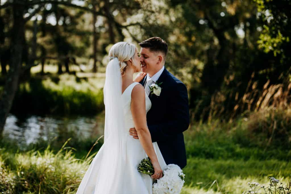 A couple kiss within the beautiful grounds of Le Petit Chateau