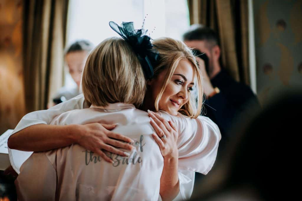 A bride and her mum share a hug