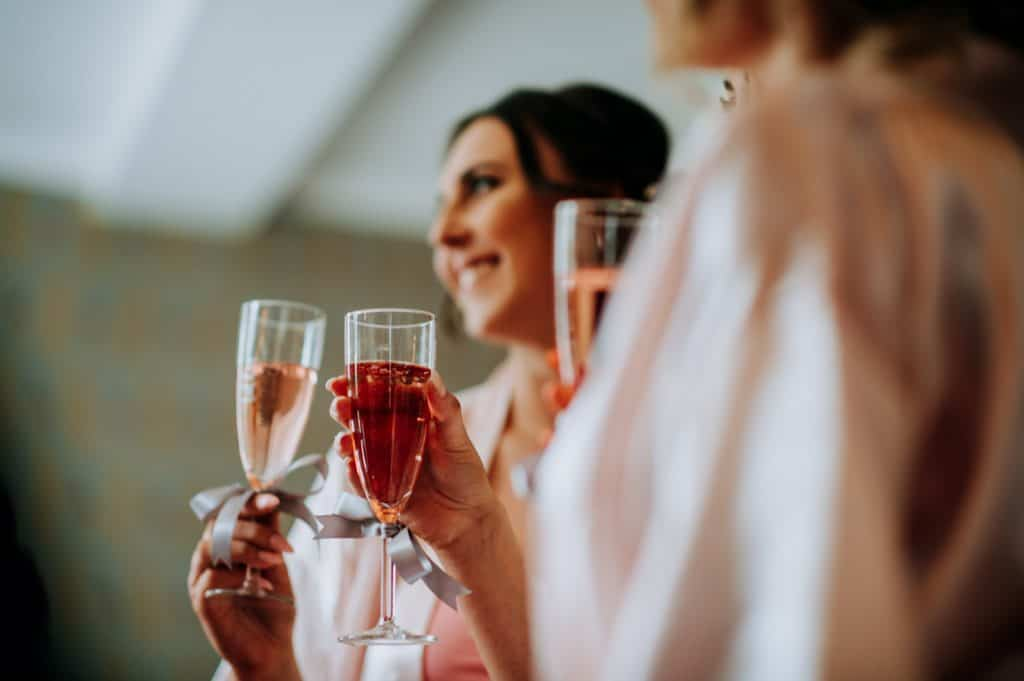 Bridesmaids share glasses of pink champagne