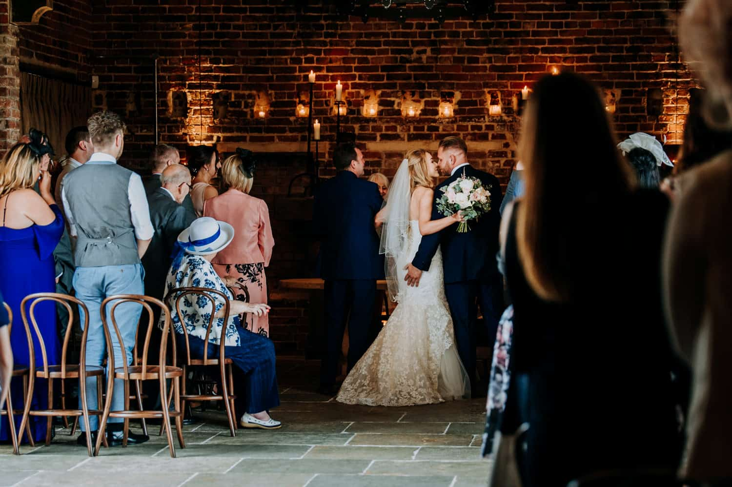 A bride and groom share a kiss at their wedding ceremony in a barn